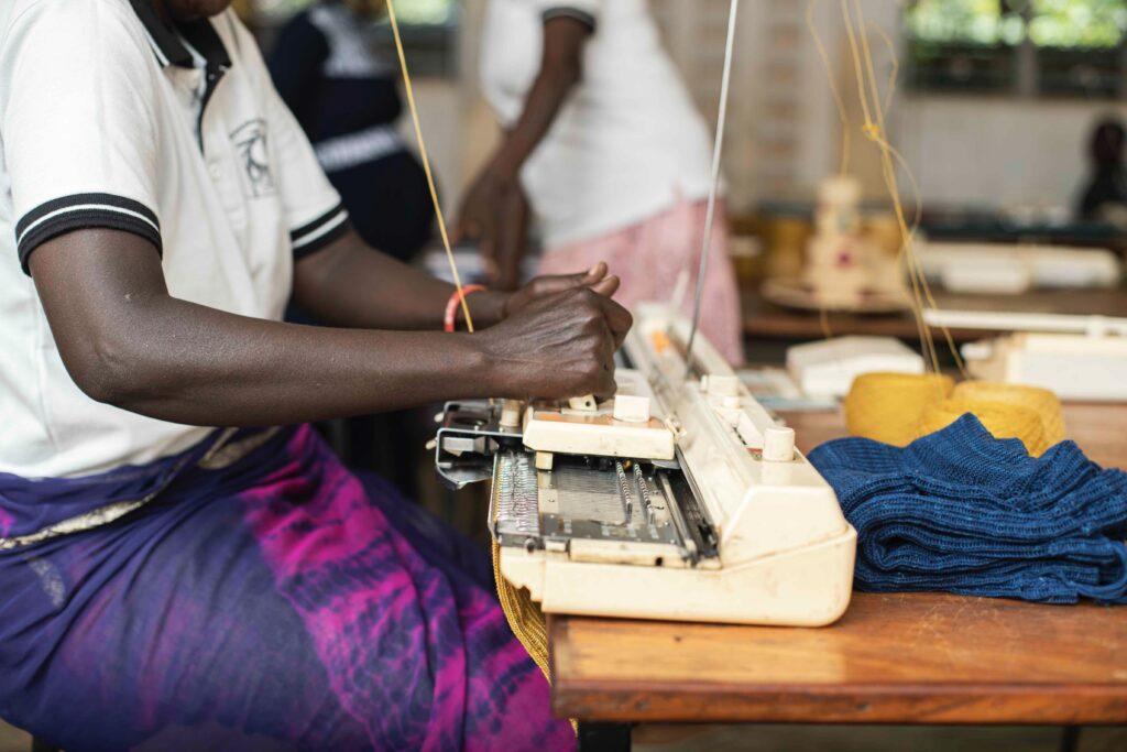 Woman at flat knitting machine at the Wawoto Kacel Workshop in Uganda.