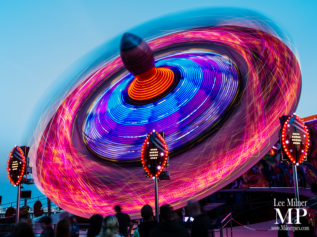 Strong red and blue digitally altered image of a spinning top fairground ride.