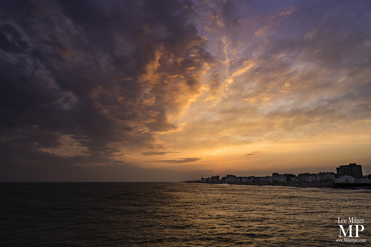 Dark sunset with dramatic cloud over a shoreline.