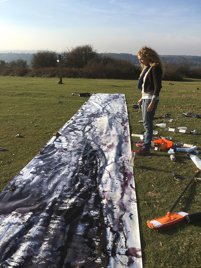 Artist Deborah Petch stands by her massive outdoor work: black ink on huge rectangular long white canvas.
