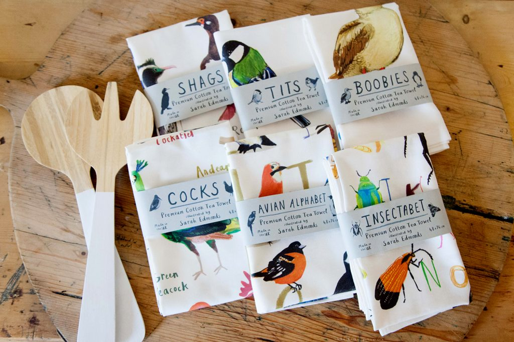 white cotton tea towels with stylised but realist brightly coloured birds printed on them, and informal handwriting style printed captions such as 'tits', 'birds', 'cocks'.